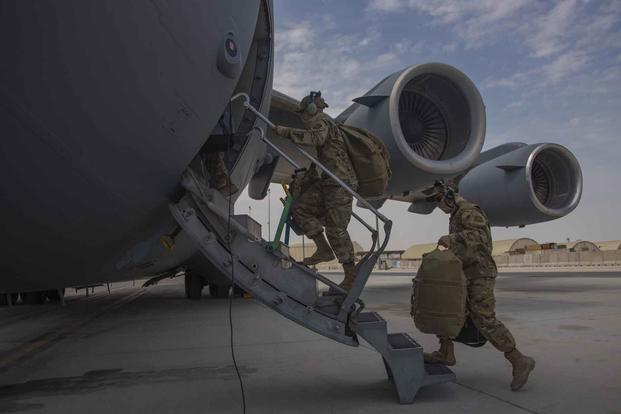 Aircrew carry their gear into a C-17 Globemaster III.