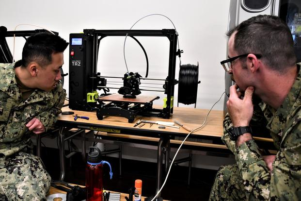 Sailors watch a 3D printer.