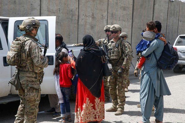 U.S. Army soldiers assigned to 3rd Brigade, 10th Mountain Division escort a young family to the terminal for check-in at Hamid Karzai International Airport in Kabul, Afghanistan.