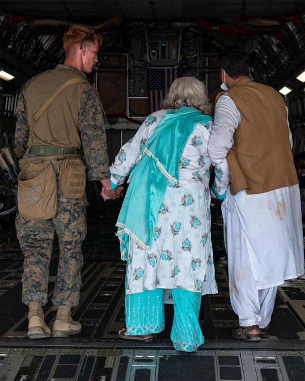 U.S. Marine Corps Marines and United States Air Force airmen lead Afghan citizens.