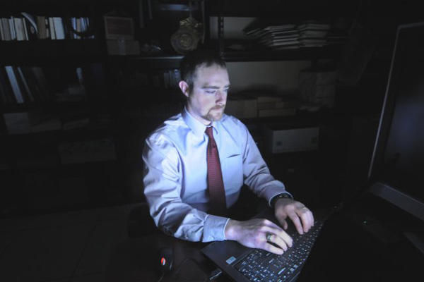 Digital forensics professional at a computer.