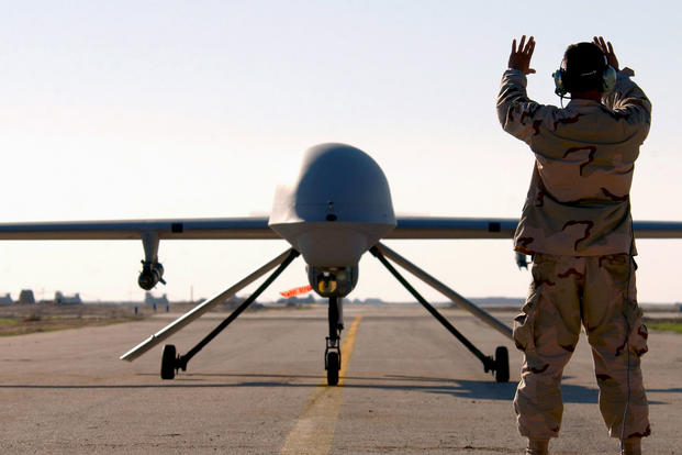 A senior airman marshals an RQ-1 Predator drone at Tallil Air Base, Iraq, in January 2008. (US Air Force photo/Suzanne Jenkins)
