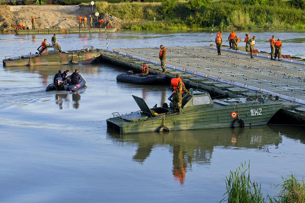 Soldiers disassemble a temporary bridge in Romania on July 17 as part of a multinational training exercise that involves more than 25,000 service members from Romania, Macedonia, and other Allied or partnered nations. (US Army photo/Justin Geiger)