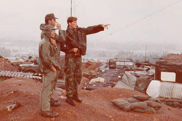 Then-Maj. William Collier, center, with his translator, Mr. Long, left, and then-Air Force Capt. Joseph Personett look out over the burm of Mo Duc District Headquarters, Vietnam, in 1972.