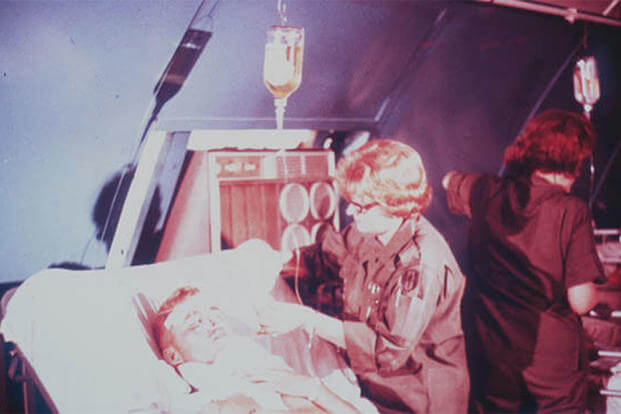 An Army nurse tending a wounded soldier in Vietnam. (U.S. Army photo)