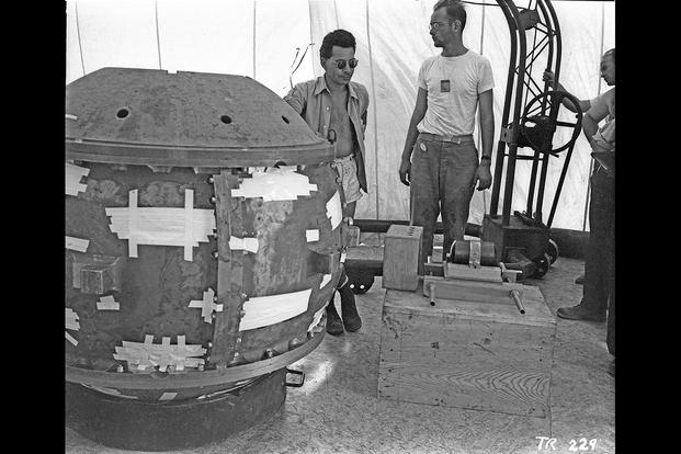 Louis Slotin (left) and Herbert Lehr with the Gadget bomb, July 13, 1945. (Los Alamos National Laboratory photo)