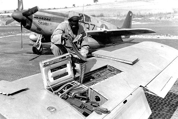 An armorer inspects ammunition in a red-tailed P-51's 50-cal. machine guns. (U.S. Air Force photo)
