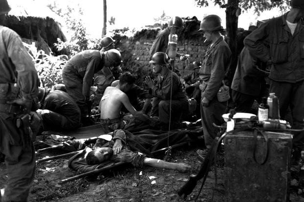 Wounded American soldiers are given medical treatment at a first aid station, somewhere in Korea. July 25, 1950. Pfc. Tom Nebbia. (Army)