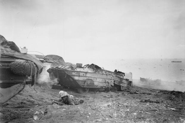 Two soldiers with their disabled DUKW take cover on the beach with the invasion fleet in the background. (Photo: National Archives)
