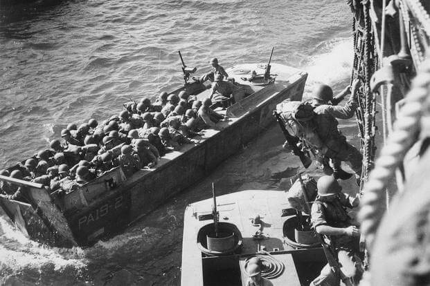 "U.S. troops go over the side of a Coast Guard manned combat transport to enter the landing barges at Empress Augusta Bay, Bougainville, as the invasion gets under way."" November 1943. (Photo: National Archives)"
