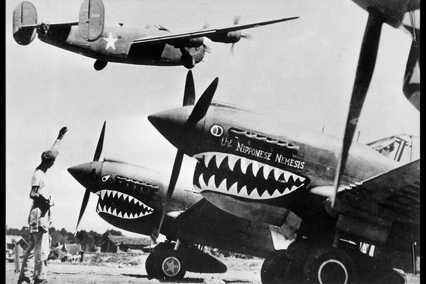 A U.S. Army Air Forces Liberator bomber crosses the shark-nosed bows of U.S. P-40 fighter planes at a U.S. base in China ca. 1943. (National Archives photo)