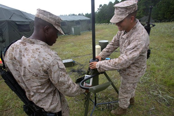 Marines repair a signal device during training.