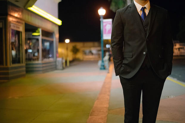 Man in a suit on a dark street.