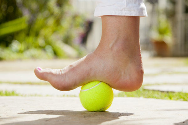 Foot massage with tennis ball