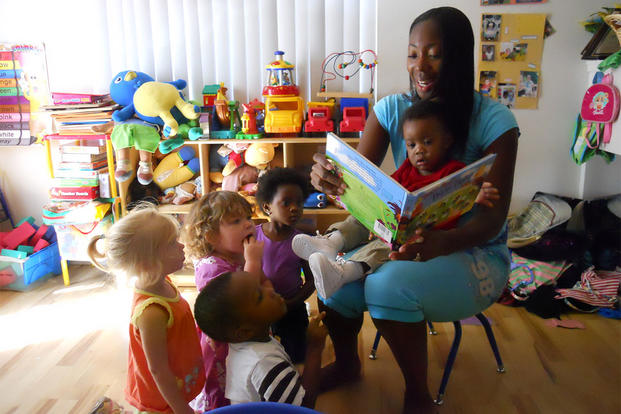 LaQuanda Alston, a childcare provider, reads a storybook to military children in her care at her home. (Photo: Rita C. Hall/U.S. Army.)