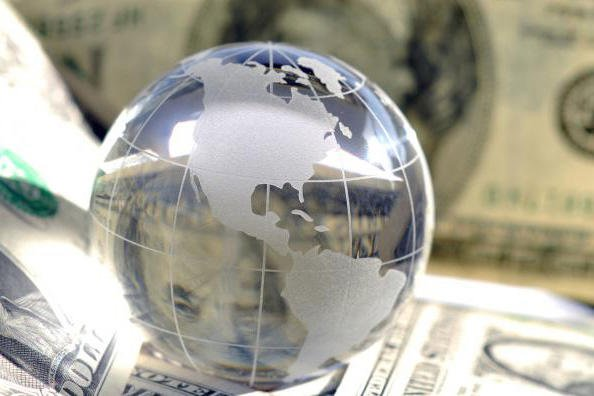 Reflective globe on money stack.