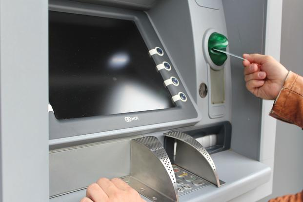 person inserting card in ATM