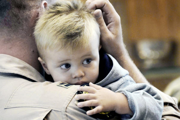 A servicemember holding his son.
