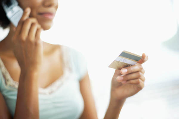 Woman on the phone holding a credit card.