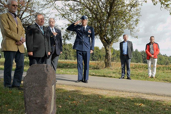Col. Harry Benham, the U.S. Air Forces in Europe-Air Forces Africa operations and plans chief, salutes during the revealing of a memorial stone for 2nd Lt. Priesley Cooper Jr. in Dietingen, Germany. (U.S. Air Force/Staff Sgt. Armando A. Schwier-Morales)