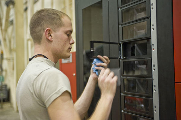 Senior Airman Bryant Fisher removes a tray of parts from a bench stock vending machine Dec. 15, 2010, in the phase hangar on Barksdale Air Force Base, La. (U.S. Air Force photo/Senior Airman Chad Warren)