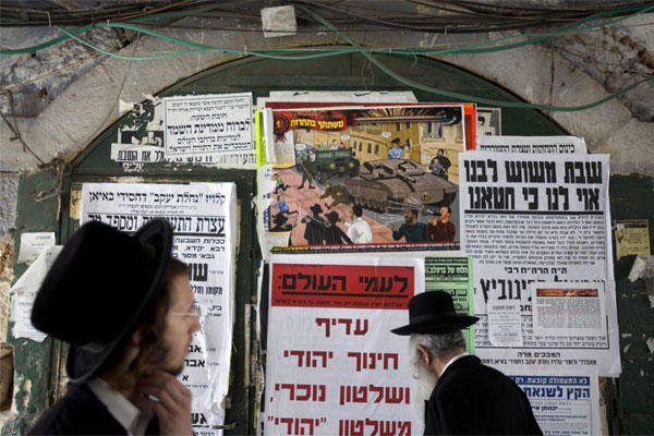ultra-Orthodox Jewish men walk past a poster in the ultra-Orthodox Jewish Mea Shearim neighborhood in Jerusalem. A large cartoon poster depicts Haredi soldiers rolling through the streets atop tanks trying to lure young boys onto their vehicles.