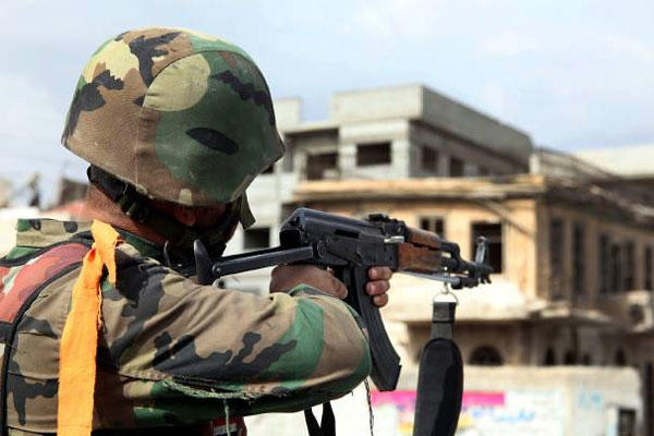 A Syrian army soldier takes his position, at a street in Sabina suburb, south of Damascus, Syria, Friday, Nov. 8, 2013.