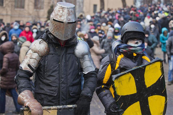 In this file photo taken on Monday, Jan. 20, 2014, Protesters clad in improvised protective gear prepare for a clash with police in central Kiev, Ukraine. (AP Photo/Evgeny Feldman, file)