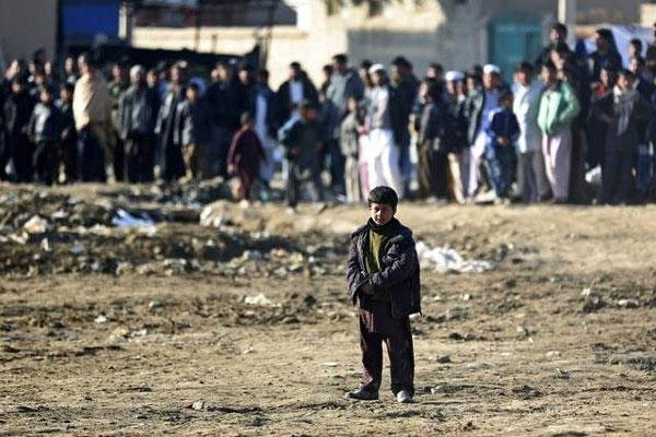 An Afghan child looks at the site of a suicide bombing that struck near a NATO convoy Monday in the Afghan capital Kabul. (Massoud Hossaini / AP)