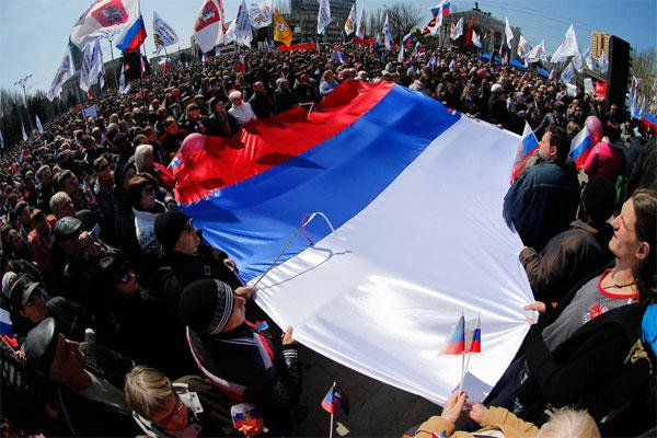 Pro-Russian activists hold a huge Russian national flag in front of the regional administration building in Donetsk, Ukraine, Sunday, April 6, 2014. (AP Photo/Andrey Basevich)
