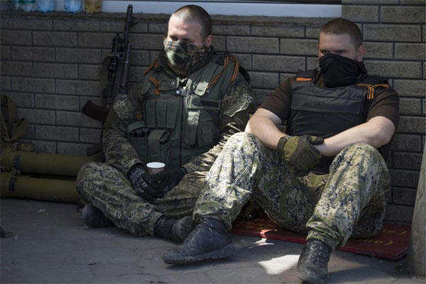 Two pro-Russian militants rest in shade at a checkpoint blocking the major highway which links Kharkiv, outside Slovyansk, eastern Ukraine, Friday, May 16, 2014. (AP Photo/Alexander Zemlianichenko)
