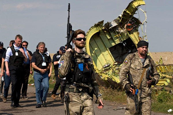 Pro-Russian rebels, followed by members of the OSCE mission, walk by plane wreckage as they arrive for a media briefing at the crash site of Malaysia Airlines Flight 17, near the village of Hrabove, eastern Ukraine, on July 22. (AP Photo/Vadim Ghirda)