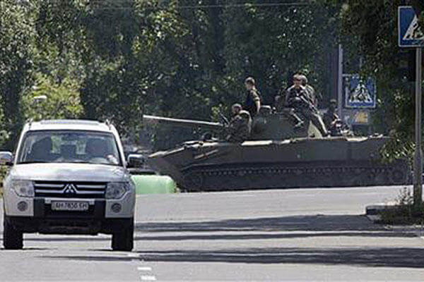 Pro-Russian fighters ride an airborne self-propelled artillery gun Nona in downtown Donetsk, eastern Ukraine Thursday, July 24, 2014.  (AP Photo/Dmitry Lovetsky)