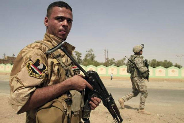 An armed Sunni militiaman wearing an Iraqi Army patch, left, and a U.S. Army soldier patrol in Samarra on Oct. 6, 2010. (Maya Alleruzzo / AP file)