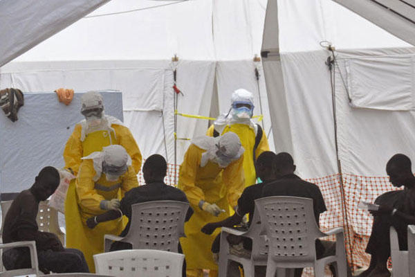 Health workers, attend to patients that contracted the Ebola virus, at a clinic in Monrovia, Liberia, Monday, Sept. 8, 2014 (AP Photo/Abbas Dulleh)