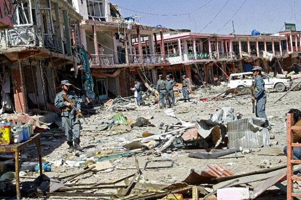 Afghan security forces walk at the site of a suicide attack in Ghazni, Afghanistan, Thursday, Sept. 4, 2014 (AP Photo/Rahmatullah Nikzad)