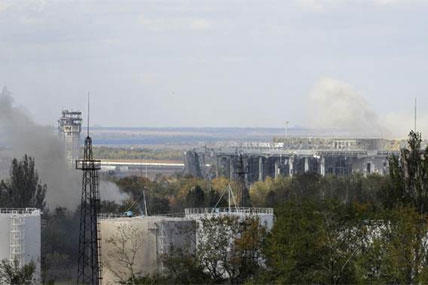 Smoke rises after artillery fire hit the airport in the town of Donetsk, eastern Ukraine, Wednesday, Oct. 1, 2014. (AP Photo/Darko Vojinovic)