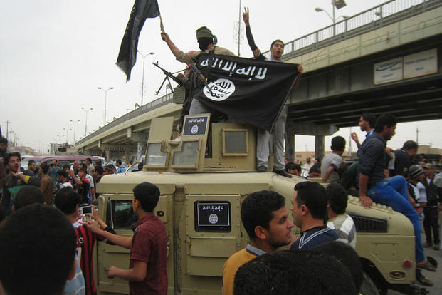 Islamic State group militants wave al-Qaida flags as they patrol in a commandeered Iraqi military vehicle in Fallujah, 40 miles (65 kilometers) west of Baghdad, Iraq. (AP Photo, File)