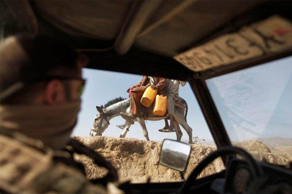 In this Sept. 12, 2009 file photo a German ISAF soldier passes children on a donkey during a patrol outside Feyzabad, east of Kunduz, Afghanistan. (AP Photo/Anja Niedringhaus, File)