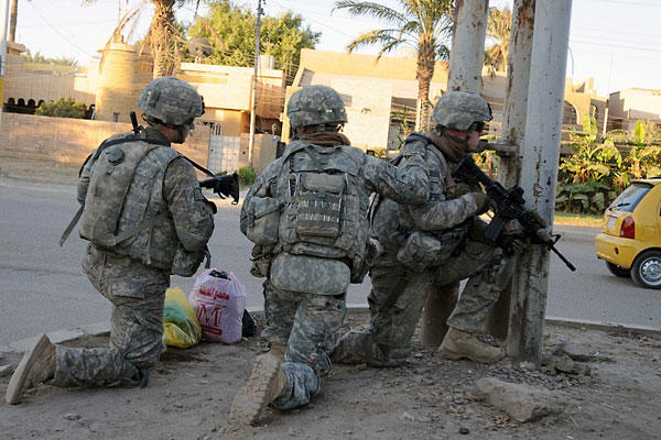 U.S. troops take a knee at a street corner before continuing a patrol in Baghdad in this file photo from Oct. 23, 2011. John Laughter/Army