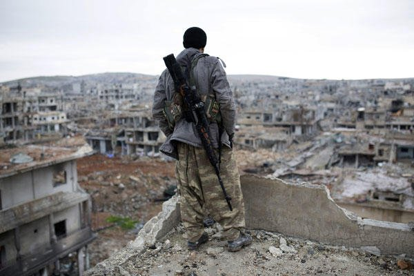 In this Jan. 30, 2015, file photo, a Syrian Kurdish sniper looks at the rubble in the Syrian city of Ain al-Arab, also known as Kobani. AP photo