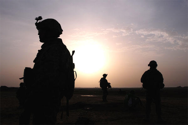 U.S. Army soldiers are silhouetted by the sun as they search a small village for anything suspicious during Operation Syme in Tikrit, Iraq, Oct. 28, 2008. U.S. Army photo by Sgt. 1st Class Kevin Doheny