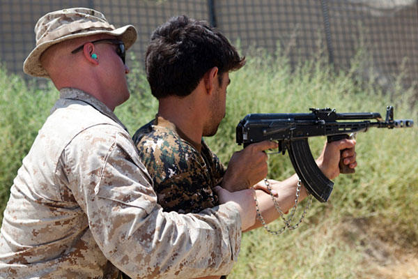 U.S. Marine Corps Cpl. Sharif Muzayen trains an Afghan Local Police recruit on the proper technique for firing his weapon on Forward Operating Base Sabit Qadam, Helmand province, Afghanistan, on July 8, 2012. Sean M. Searfus/Marine Corps