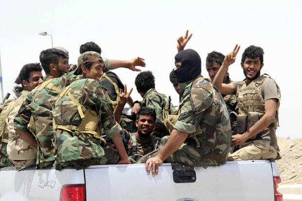 In this Saturday, May 23, 2015, photo, Shiite militiamen arrive in Khalidiya to support Sunni tribal fighters and local policemen as they defend their city against Islamic State group militants. Associated Press photo