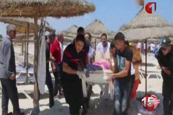 In this screen grab taken from video provided by Tunisia TV1, injured people are treated on a Tunisian beach Friday June 26, 2015.(Tunisia TV1 via AP)