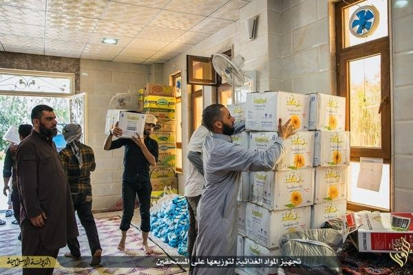 ISIS members prepare foodstuff on June 19 to be handed over to the poor during the Muslim holy month of Ramadan in Mosul, northern Iraq.(Source: AP)