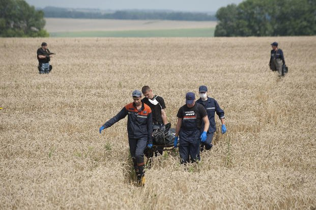 Emergency workers carry the body of a victim on July 19, 2014 at the crash site of a Malaysia Airlines jet near the village of Hrabove, eastern Ukraine.(AP Photo/Evgeniy Maloletka, file)