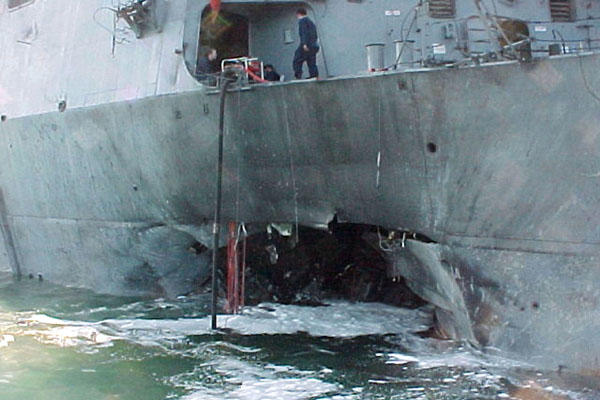 Port side view showing the damage sustained by the USS Cole on Oct. 12, 2000, after a terrorist bomb exploded during a refueling operation in the port of Aden, Yemen. DoD photo.