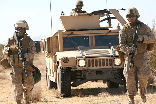 Pfc. Justin Jones and Lance Cpl. Martin Carranza lead their Humvee on an alternate route to bypass a possible simulated improvised explosive device. (Marine photo)
