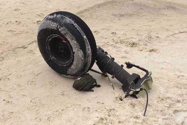 Part of a wheel assembly of what could be the wreckage of a UH-60 Black Hawk helicopter sits on on Riviera Beach in Navarre, Fla., Wednesday, March, 11, 2015. (AP Photo/Northwest Florida Daily News, Jennie McKeon)